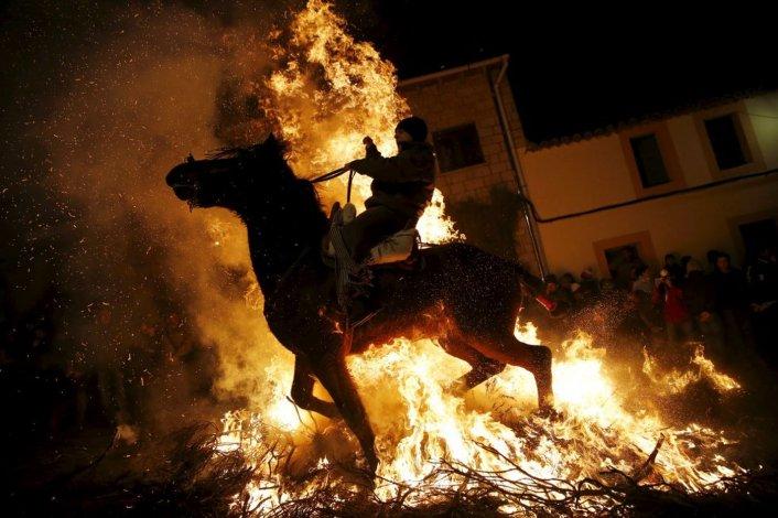 Un hombre monta a caballo a través de las llamas durante la celebración religiosa Luminarias en la víspera del día de San Antonio