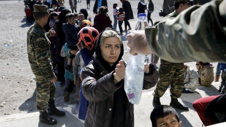 Una migrante recibe una porción de comida y agua en un campamento en Schisto