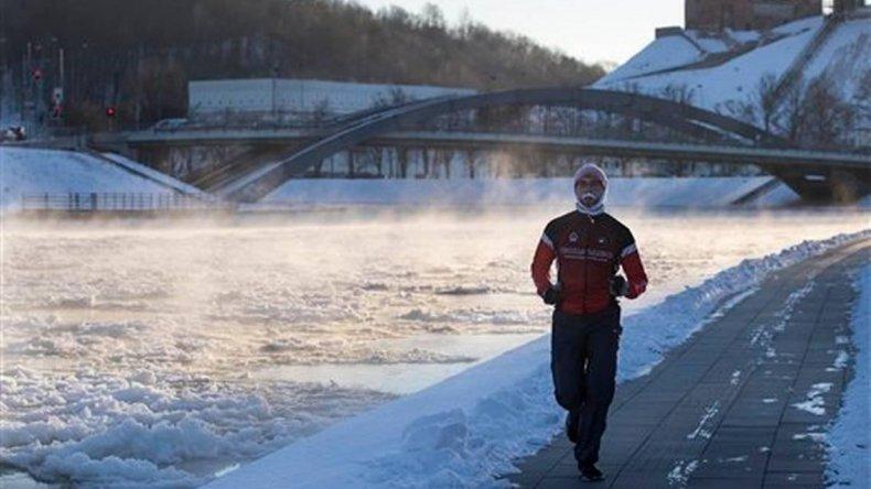 Un hombre practicando running mientras el agua presenta grandes porciones de hielo.