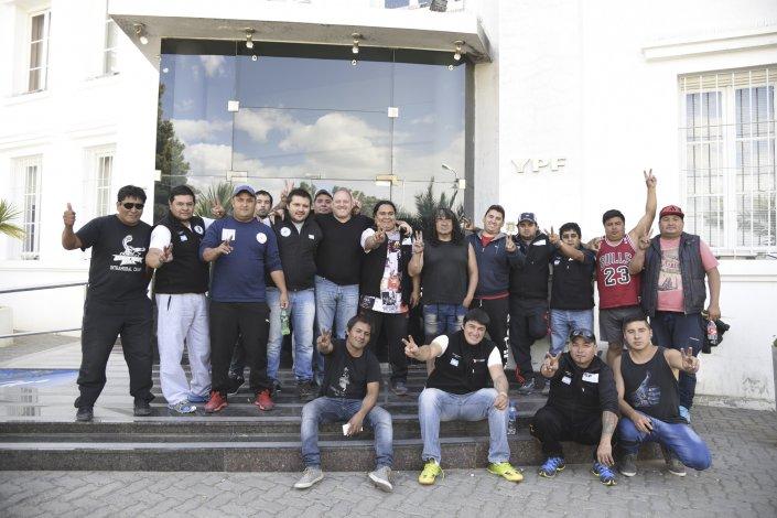 Los trabajadores apostados ayer por la tarde afuera de las oficinas de YPF.