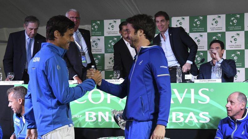 Guido Pella se saluda con Paolo Lorenzi. Ambos animan el primero de los cinco puntos en Parque Sarmiento.
