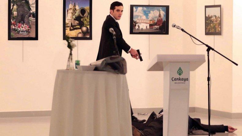 El asesino acaba de ejecutar al embajador y ahora mira hacia el público que asistía al evento.