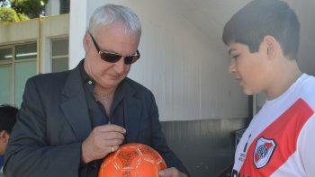 El Beto Alonso le autografía una pelota naranja a Ciro.