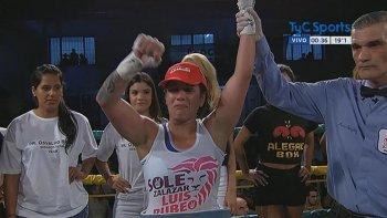 El árbitro del combate le levanta el brazo izquierdo en señal de triunfo a La Leona Bustos.
