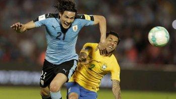 Edinson Cavani disputa el balón con el brasileño Dani Alves.