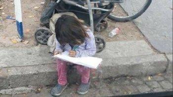 una nena hace los deberes mientras pide limosna