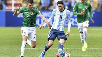 Angel Di María con el balón marcado por Juan Carlos Arce y atrás se observa a Raúl Castro.