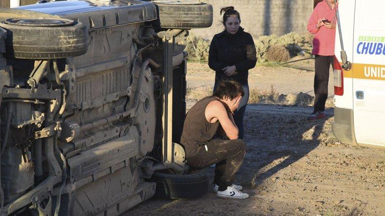 El conductor se lamenta sentado sobre un neumático del vehículo.