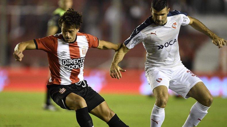 Matías Aguirregaray disputa el balón con Emmanuel Gigliotti en el partido jugado anoche en Avellaneda.