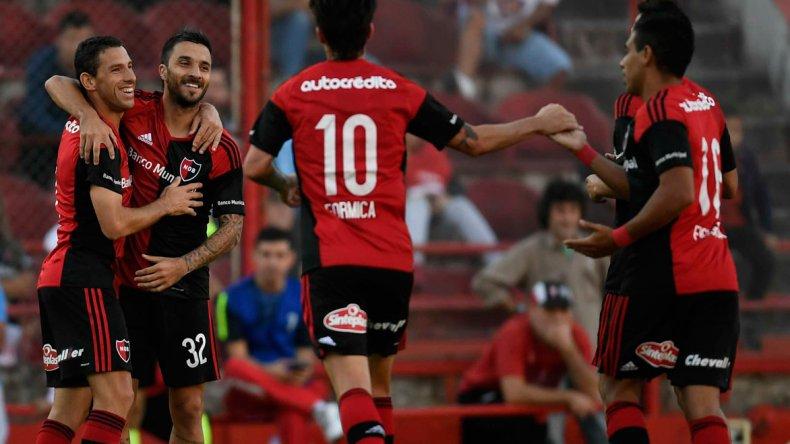 Maxi Rodríguez felicita a Nacho Scocco y se unen al festejo Mauro Formica y Víctor Figueroa.