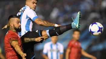 Gustavo Bou disputa el balón con Gastón Aguirre en el partido que anoche Temperley le ganó a Racing.
