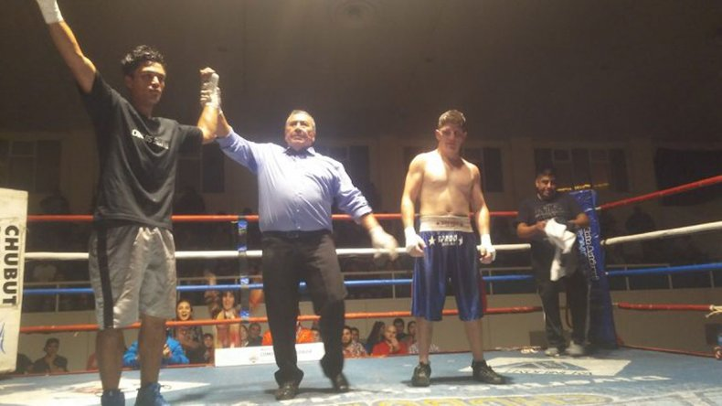 El árbitro del combate le levanta el brazo a Carlos Santana en señal de victoria.