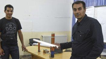 Luis Dulcich y su hijo Juan experimentan en el Colegio Perito Moreno con un sistema inalámbrico de energía.