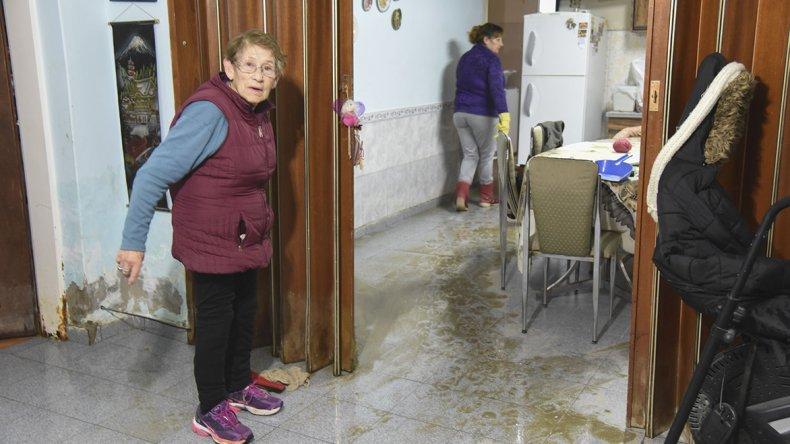 Una de las damnificadas muestra cómo el agua servida anegó su vivienda.