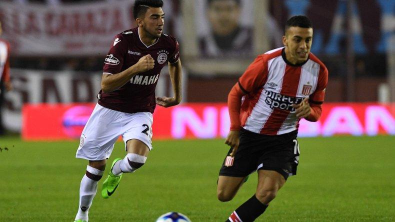 Damián Moreno se lleva el balón ante la marca de Lucas Rodríguez en el partido jugado anoche en cancha de Lanús.