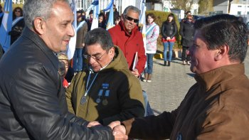 Los ex soldados conscriptos correntinos, Mario Báez y Miguel Barría se estrechan la mano al finalizar el acto. Atrás se observa a otro ex combatiente de Caleta Olivia, Pablo Carrizo y al comisionado de fomento Jorge Soloaga.