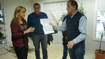Mariana Dahinten recibe el subsidio de manos del intendente Carlos Linares.
