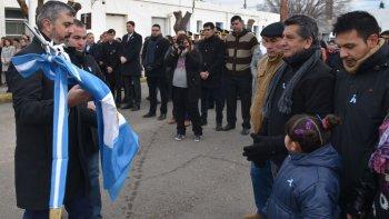El diputado Sergio Bucci y el secretario de Gobierno de la comuna, José Luis Lacrouts, entregaron una de las banderas de ceremonias a dirigentes de la vecinal del barrio El Mirador.