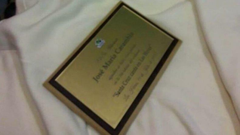 La placa tirada arriba de la cama del hotel.