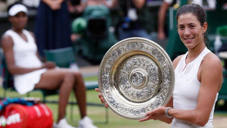 Garbiñe Muguruza posa orgullosa con el trofeo ganado ayer en Wimbledon.