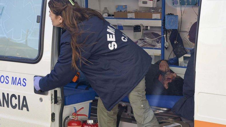 El herido de arma blanca recibe asistencia médica en la ambulancia que luego fue chocada por un Ford Fiesta.