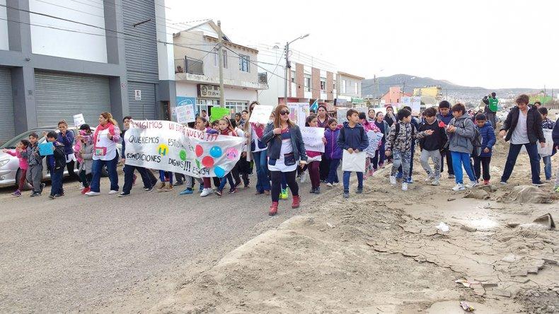 La comunidad educativa de la Escuela 154 ayer al mediodía marchó por la avenida Kennedy en reclamo de la reconstrucción de su edificio.