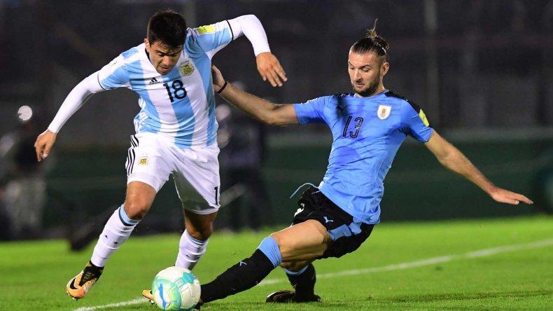 Marcos Acuña intenta escaparse con el balón marcado por Gastón Silva en el partido jugado anoche en Montevideo.